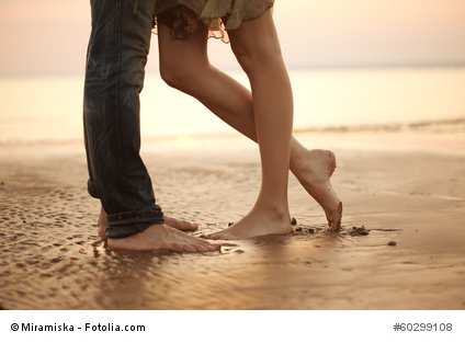 A loving young couple hugging and kissing on the beach. Lovers m